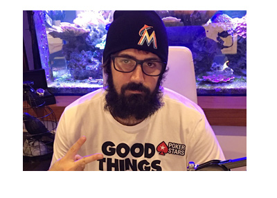 Poker player - Jason Mercier - giving a peace sign to his listeners.  Radio show.