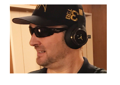 Phil Hellmuth caught walking down the hall with an Aria hat and dark headphones.