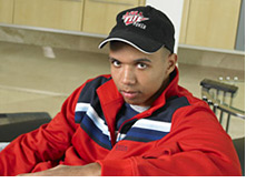 promotional photo of poker player phil ivey - relaxing in a red track suit - on the couch - with a full tilt hat